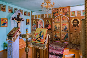 Prayer altar with handwritten icons in the interior of the village Russian church.