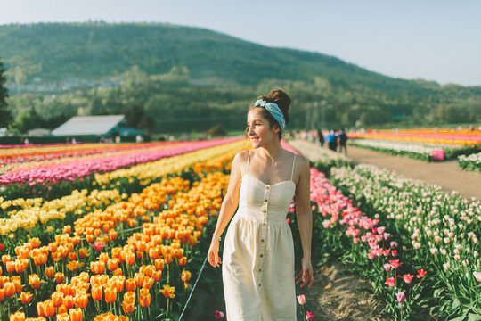 A beautiful woman walking through a field of tulips in Spring.
