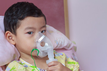 Close-up sick 3 years old child holding nasal mask with respiratory problem in hospital room. Asian boy patient inhalation therapy by the mask of inhaler with soft stream smoke from bronchodilators.