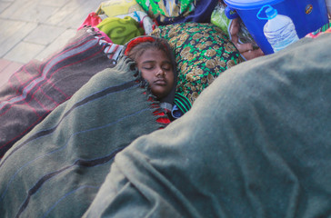 A girl wrapped in a blanket sleeps on a road divider on a cold winter morning in New Delhi