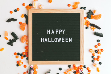 A letter board that says 'Happy Halloween' surrounded by Halloween candy.