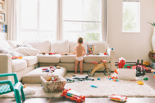 A little boy playing in a messy living room.