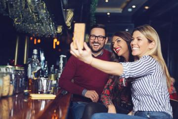 Three friends taking selfie in a bar.