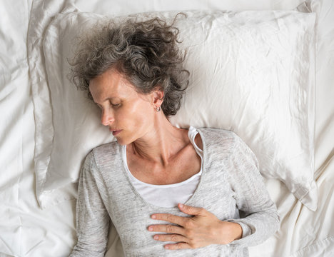 High angle close up of middle aged woman with grey hair sleeping on silk pillow case and messy sheet (selective focus)
