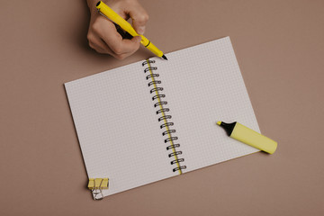 Hand writing in notepad using a pen, on gray background