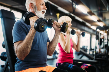 Senior fit man and woman doing exercises in gym to stay healthy