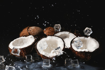 Halves of ripe coconuts, ice cubes and splash of milk on dark background