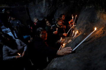 Christians light candles as they celebrate Saint Barbara's Day at the Church of Saint Barbara in the village of Aboud, in the Israeli-occupied West Bank