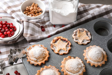 Baking tray with tasty mince pies on table
