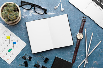Opened notebook and other office equipment such as computer, pencil,  and glasses on wooden office desk.
