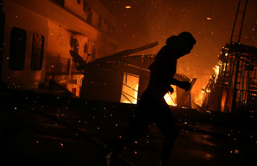 A resident is seen during a fire at Educando neighbourhood, a branch of the Rio Negro, a tributary to the Amazon river, in the city of Manaus