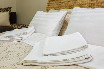 Bath towels and pillows on the bed in Interior of the modern bedroom in loft flat apartments in light color style