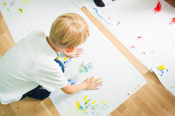 Top view of boy painting with his hands on the sheet of paper