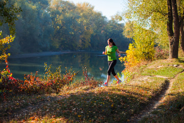 Jogging woman on the autumn pond and forest background