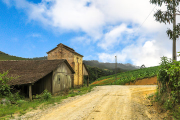 Barn next to dirt road, with mountain and tobacco plant in the background, blue sky with clouds, Presidente Nereu, Santa Catarina