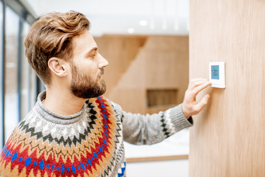Man in sweater feeling cold adjusting room temperature with electronic thermostat at home