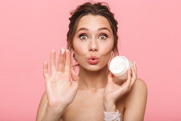 Pretty young woman posing isolated over pink wall background take care of her skin with cream.