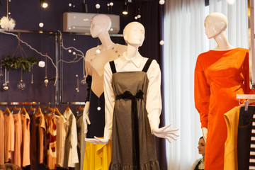 clothing store, beautiful dresses on mannequins, clothes lines, sequins and sparkles
