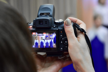May 12, 2018. Krasnoyarsk. Russia. A woman shoots her child's performance at a concert on the camera fujifilm finepix hs 35. Video will be remembered for her daughter