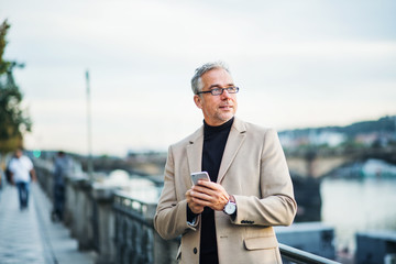 Mature businessman with smartphone standing by river in Prague city, using smartphone.