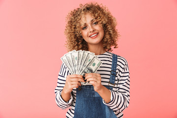 Photo of surprised curly woman 20s holding fan of dollar money while standing, isolated over pink background