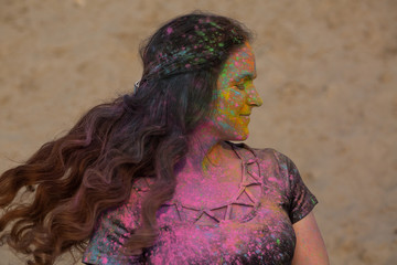 Magnificent brunette girl with long fluttering hair wearing black t shirt covered with colorful dry paint Holi at the desert