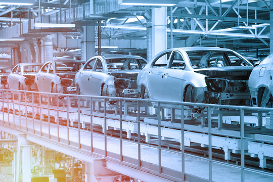 Car bodies are on Assembly line. Factory for production of cars in blue. Modern automotive industry. Blue tone