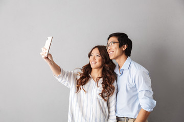 Happy asian couple standing isolated over gray