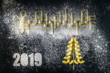 Musical Christmas Italian pasta 2019  in the form of notes and a Christmas tree, isolated on a black textural background.