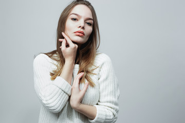 Beautiful long-haired girl in a white knitted sweater is posing on the white background in the studio