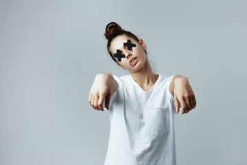Girl dressed in white t-shirt with black crosses of adhesive tape on the eyes is posing like a zombie on the white background in the studio
