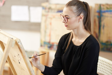 Pretty fair-haired girl in glasses dressed in black blouse sits at the easel and paints a picture in the art studio