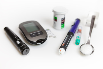 Diabetic set of lancet with spare needles, glucometer, strips, box of spare strips, pen injector, spare insulin and sugar on spoon isolated on white background