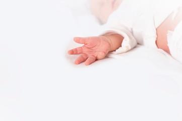 Baby liegt auf dem Rücken und streckt die Finger einer Hand