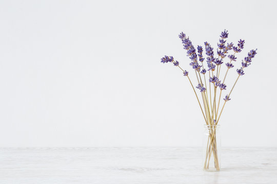 Dried purple lavender in vase on table at light gray wall. Mockup for positive idea. Empty place for inspirational, emotional, sentimental text, quote or sayings. Front view.