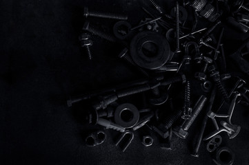 Abstract of Used Metallic knot screw nuts and nail bolts on dark background
