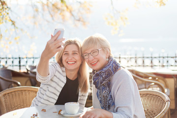 Two beautiful blonde women take selfie. Mother and her adult daughter have meeting in autumn street cafe outdoor. Happy senior woman and young girl are smiling and using mobile phone.