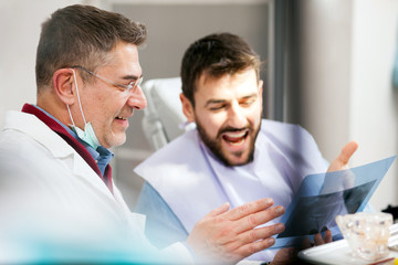 Smiling mature male dentist and young patient looking at teeth x-ray image after successful medical intervention. Health care and medicine concept