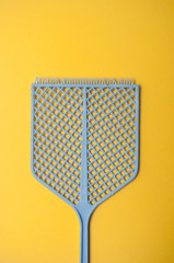 closeup of blue fly swatter on yellow  background