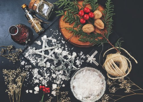 Two salt pentagrams as Yule tree ornaments. Messy wiccan altar with winter solstice decorations and nature elements like dried herbs and flowers. Pentagrams with salt crystals on them for protection