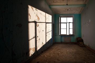 Open window in an empty abandoned room, harsh shadows.