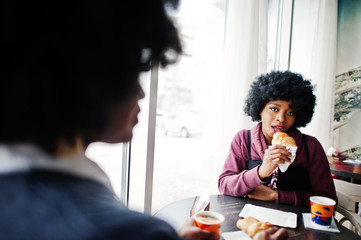 Two curly hair african american woman wear on sweaters sits at table cafe , eat croissant and drink tea.