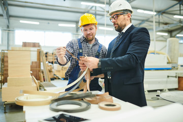 Fototapeta Serious modern investor in hardhat standing at table and analyzing quality of manufactured products with young engineer obraz