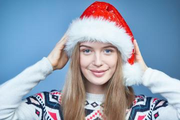 Closeup of a woman wearing Santa hat, looking at camera