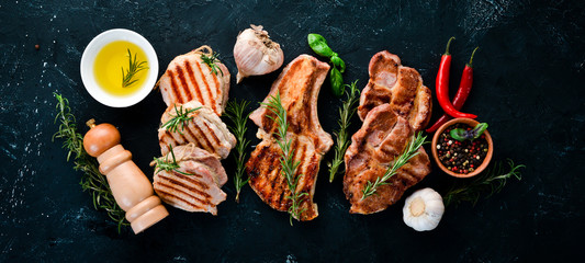 Grilled Meat. Seth meat. Grill, barbecue. On a black stone background. Top view. Free copy space. Wall mural