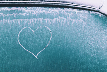 Heart drawn on frozen iced car window. Frost on glass. Copy space. Valentines Day, love and care concept. Cold winter season.