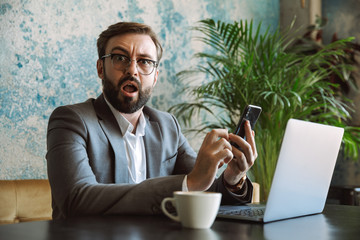 Shocked young businessman dressed in suit working