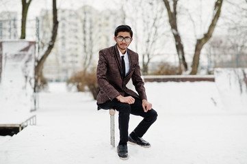 Stylish indian student man in suit and glasses posed at winter day outdoor.