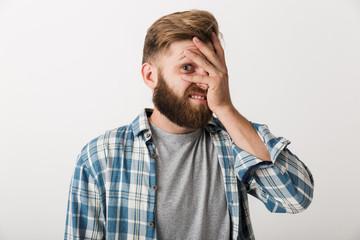 Ashamed bearded man dressed in plaid shirt