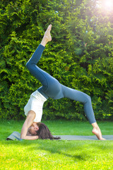 beautiful adult woman doing yoga at summer morning